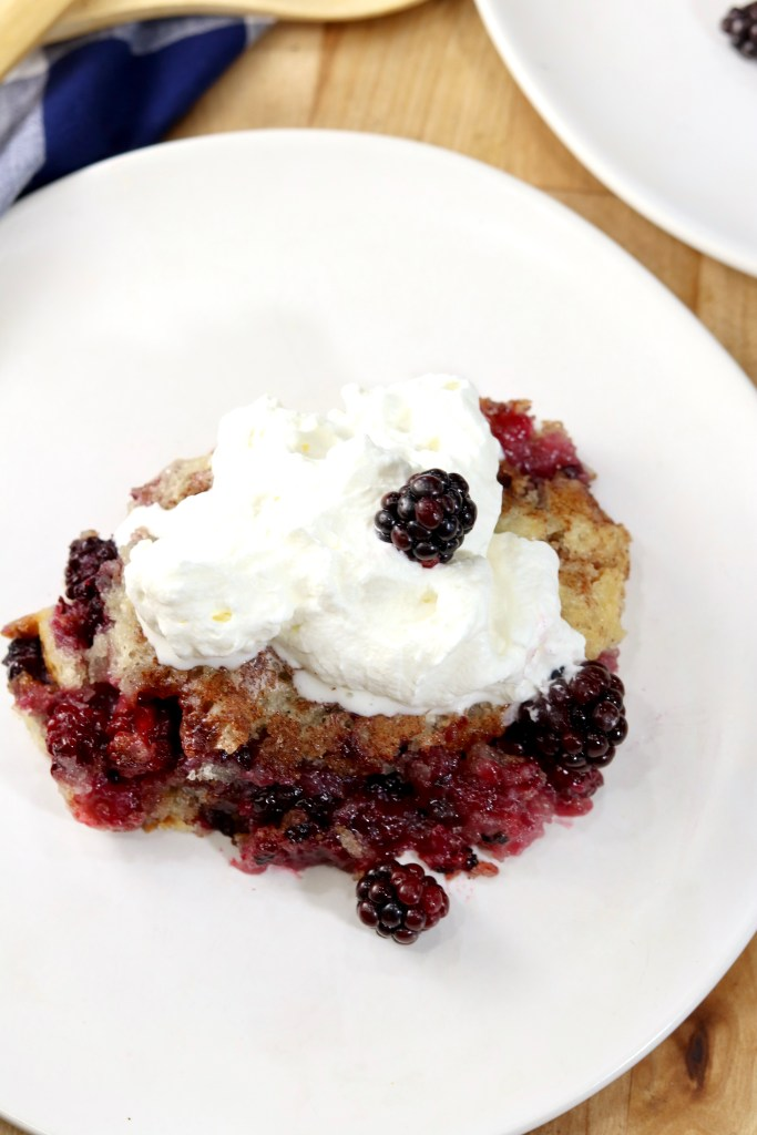 Blackberry cobbler with whipped cream on a white plate