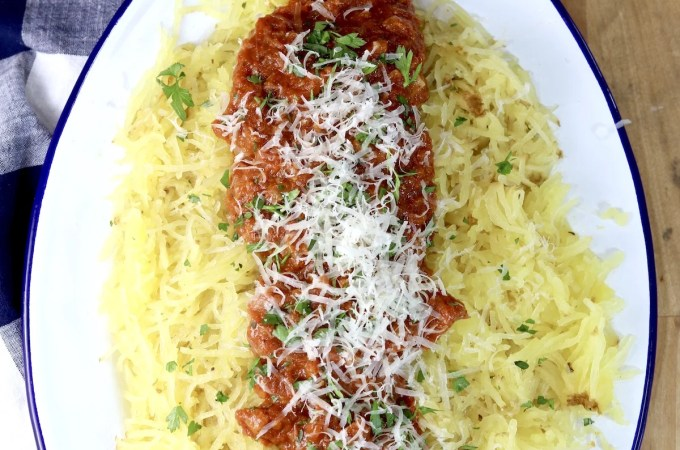 Roasted Tomato Sauce served over spaghetti squash on an oval platter, garnished with grated parmesan and green herbs