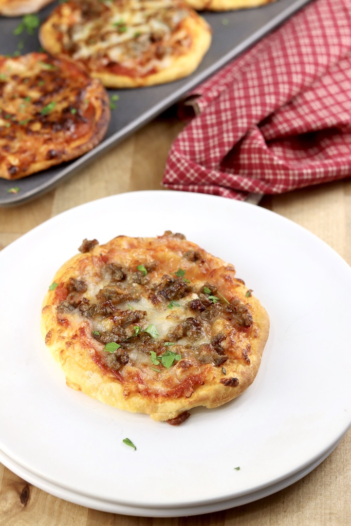 Air Fryer Mini pizza on a white plate - tray of pizzas in background with red napkin