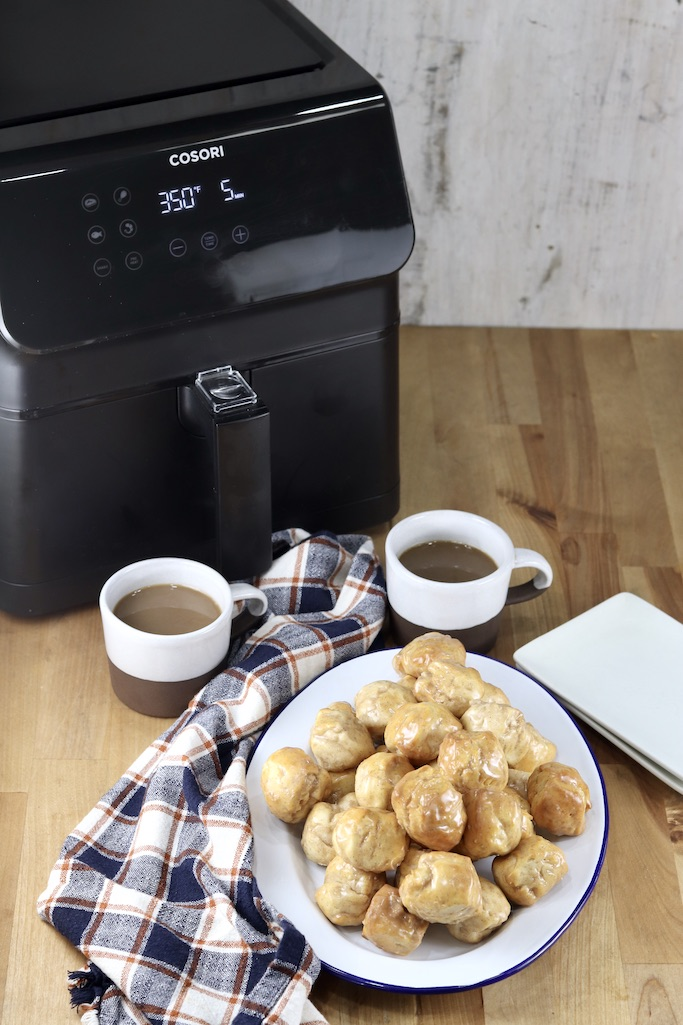 Cosori Air Fryer with 2 cups of coffee, donut holes on a platter