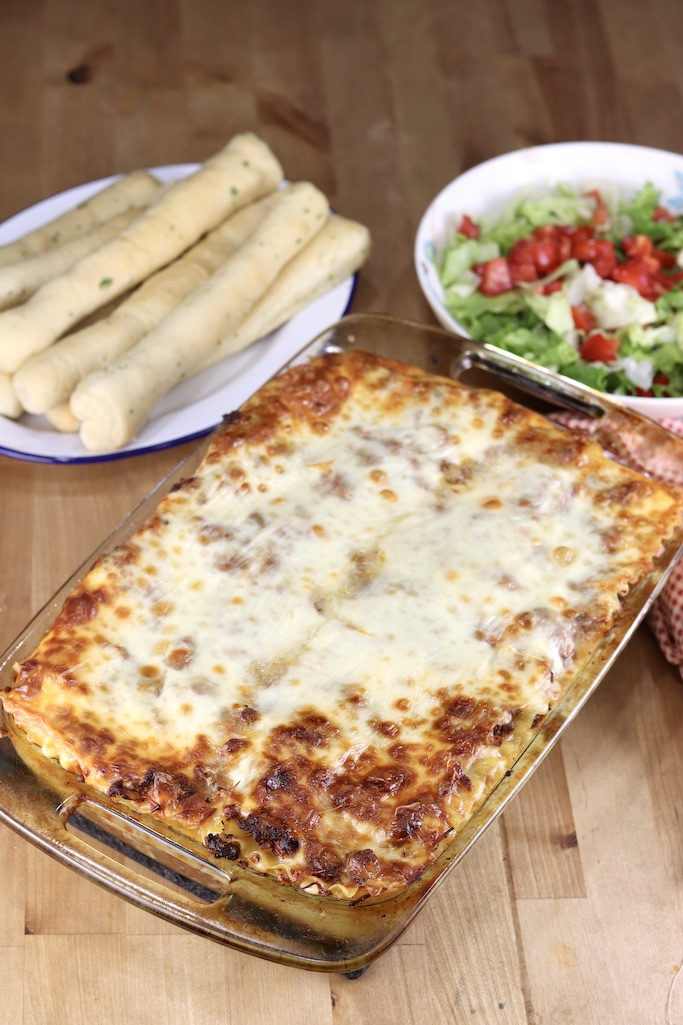 9 x 13 casserole with baked lasagna, plate of breadsticks, salad with tomatoes