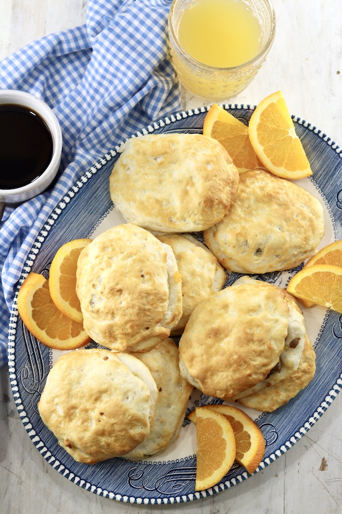 Air Fryer Sausage Biscuits on a platter with slices of fresh oranges, coffee and juice