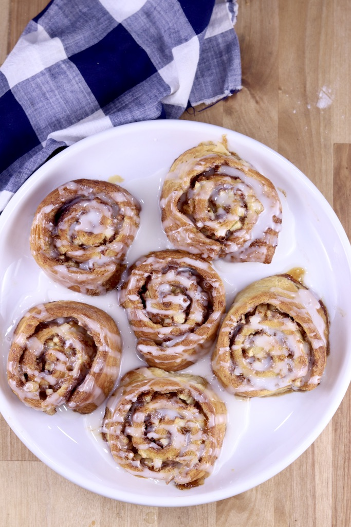 Air Fryer Apple Cinnamon Rolls overhead view on a white plate with blue napkin