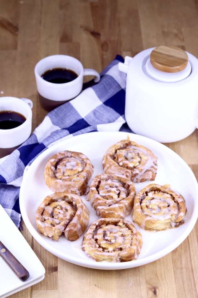 Apple Cinnamon Rolls on a white plate, white coffee pot and 2 cups of coffee with a blue napkin