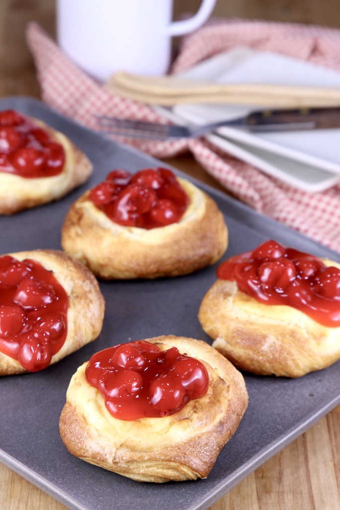 Cherry Cheese Danishes on a platter, red napkin and saucers in background