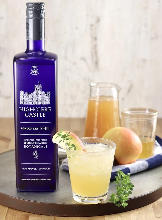 Highclere Castle Gin with apple cider, honey syrup, gin cocktail, whole apple and fresh thyme sprigs