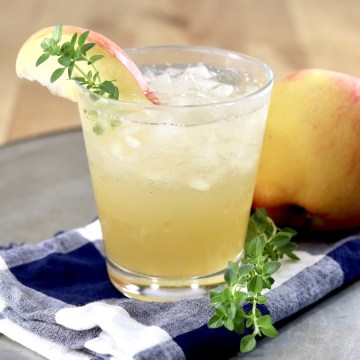 Apple Cider Gin Cocktail -small glass with ice, apple and thyme garnish