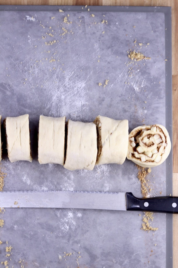Sliced cinnamon roll dough with serrated knife below on gray board