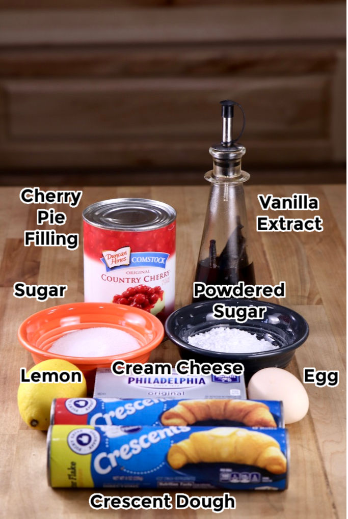 Ingredients for Cherry Cheese Danish with text labels: crescent dough, sugar, powdered sugar, vanilla, lemon, egg, cream cheese, cherry pie filling