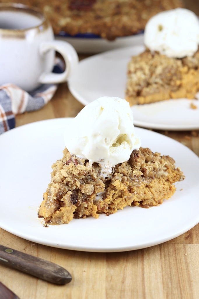 slice of pumpkin pecan crisp dessert with vanilla ice cream scoop on top