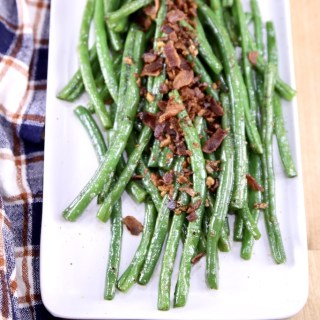 bacon green beans on a white platter with plaid napkin