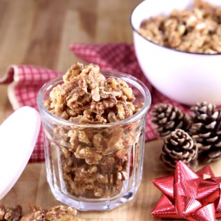 Candied Walnuts in a small jar for a gift, pine cones and red bow with a white bowl of walnuts
