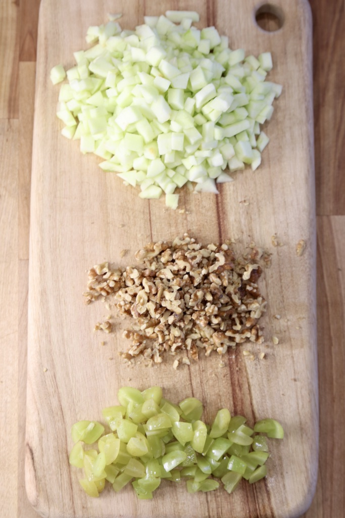 cutting board with diced apples, chopped walnuts and chopped grapes
