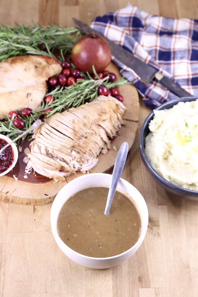 Bowl of gravy, platter of sliced turkey breast, mashed potatoes