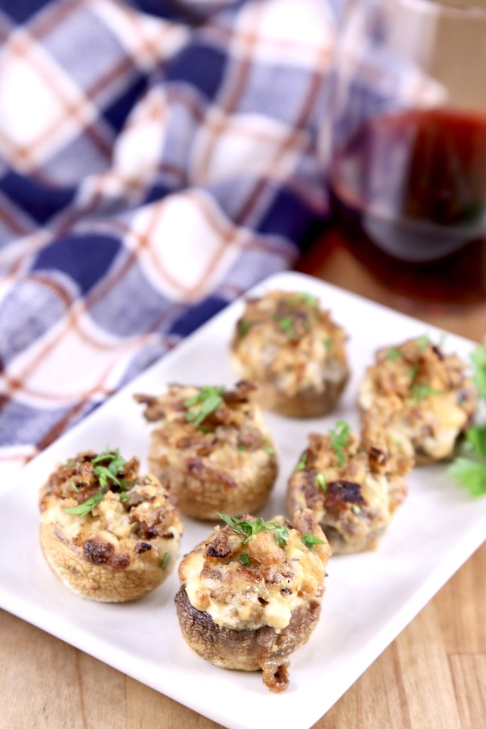 Plate of mushrooms stuffed with cheese and sausage with a plaid napkin