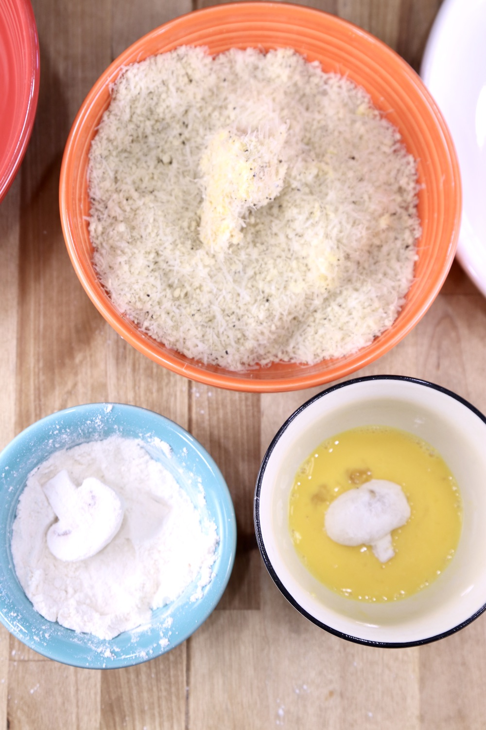 Bowls for breading mushrooms with flour, egg, and panko bread crumb mixture, mushroom in each