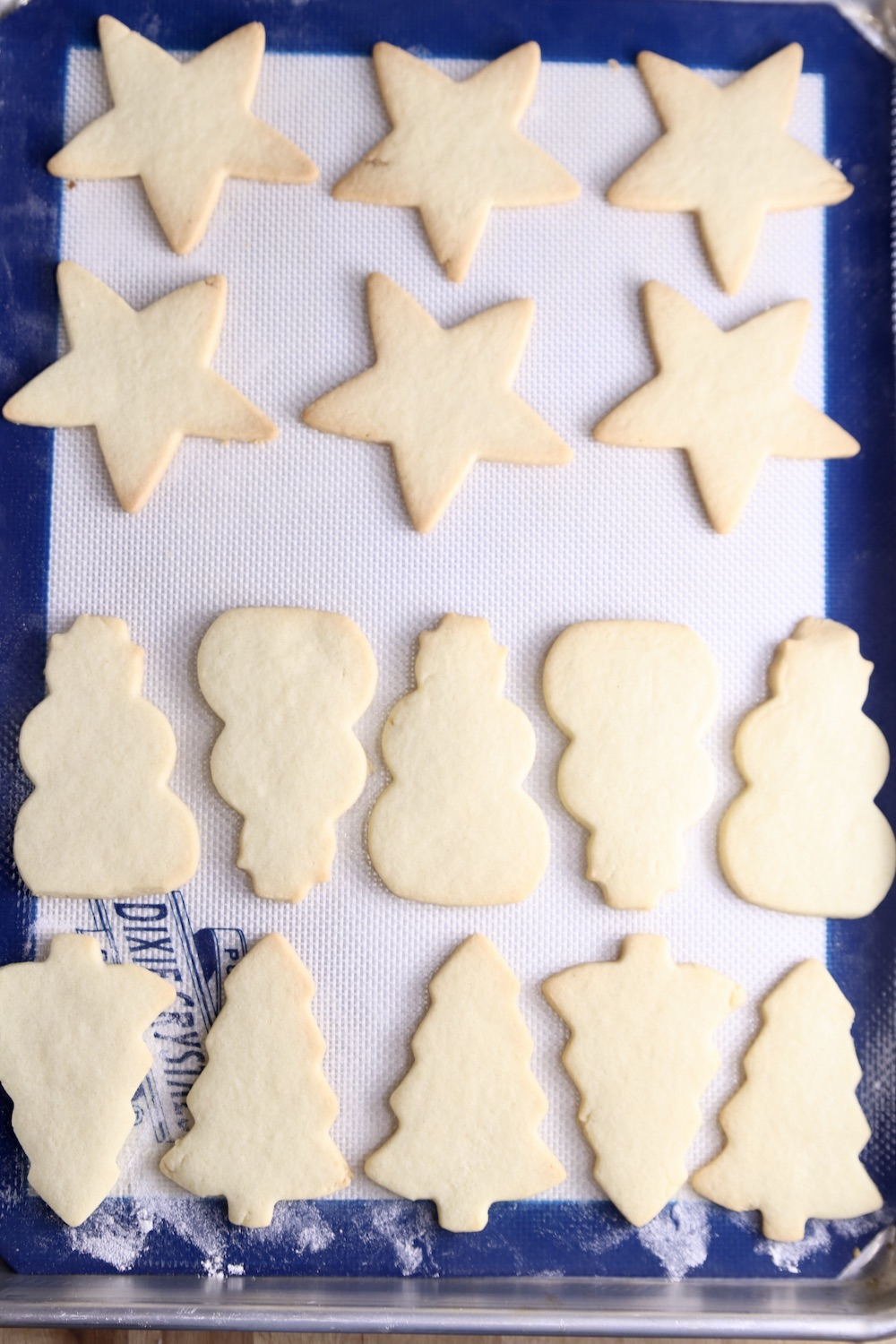 Baked Cut out sugar cookies on a baking sheet. Stars, snowmen and trees.