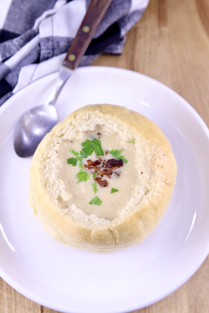 Beer Cheese Soup with bacon and parsley on a saucer with a soup spoon