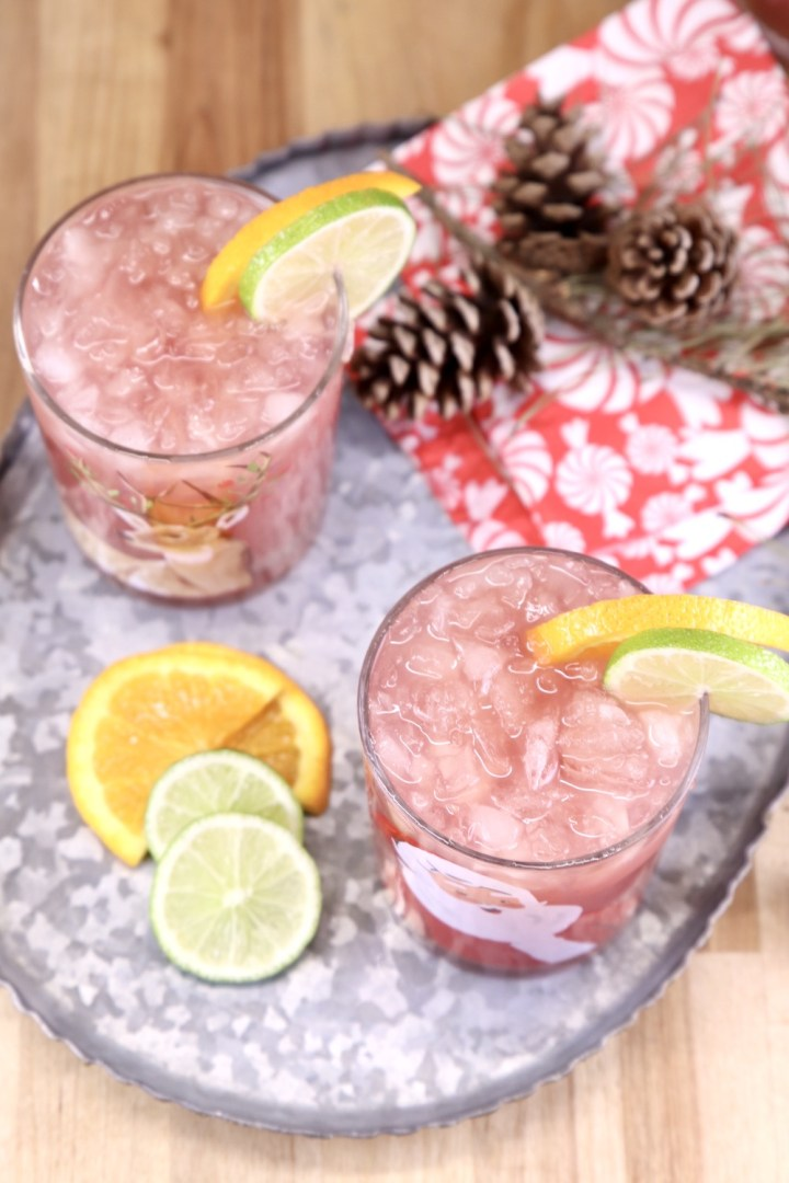 Overhead view of 2 glasses of punch on a platter with pinecones