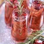 Cranberry mimosa cocktails on a tray with rosemary and cranberry garnish