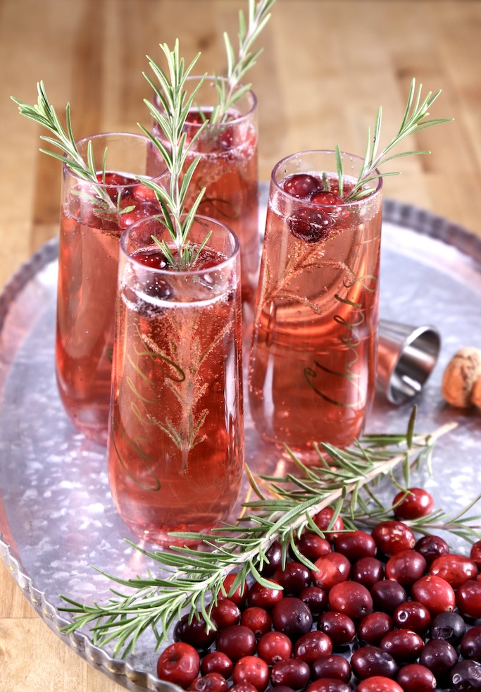 4 cranberry mimosa cocktails on a tray with fresh rosemary and cranberries