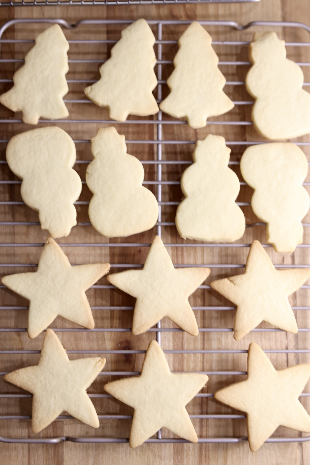 Wire rack of cut out sugar cookies. Trees, snowmen, stars.
