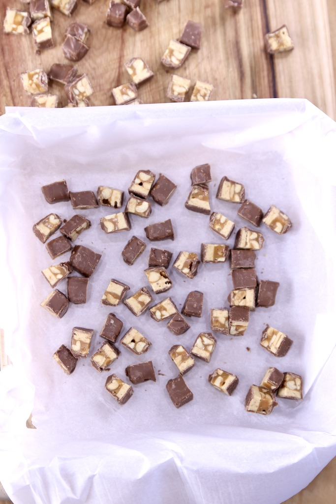 square dish lined with parchment paper, with chopped snickers bars