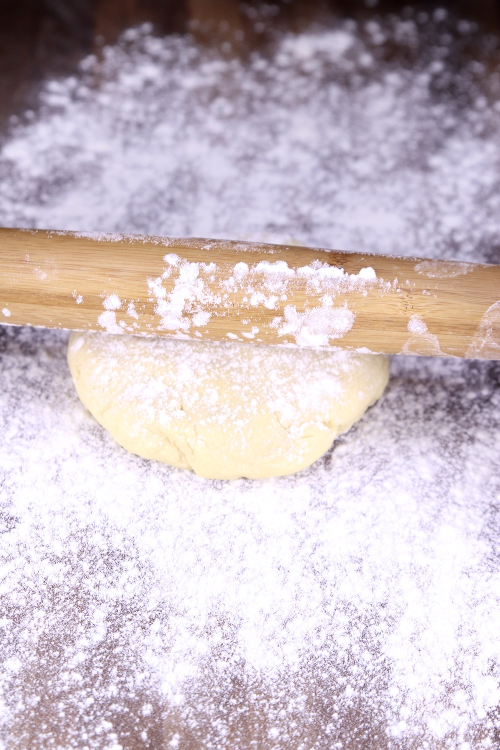 Rolling pin rolling sugar cookie dough on a well floured board