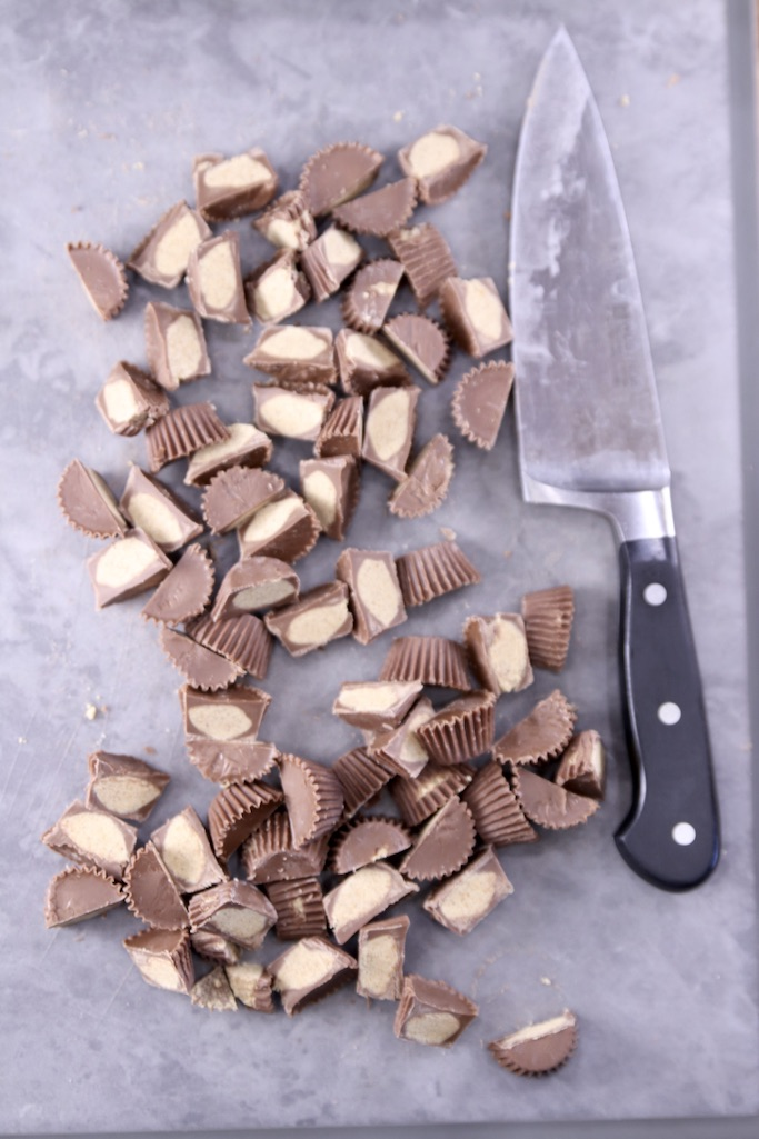 Mini peanut butter cups cut in half on a gray cutting board with a knife