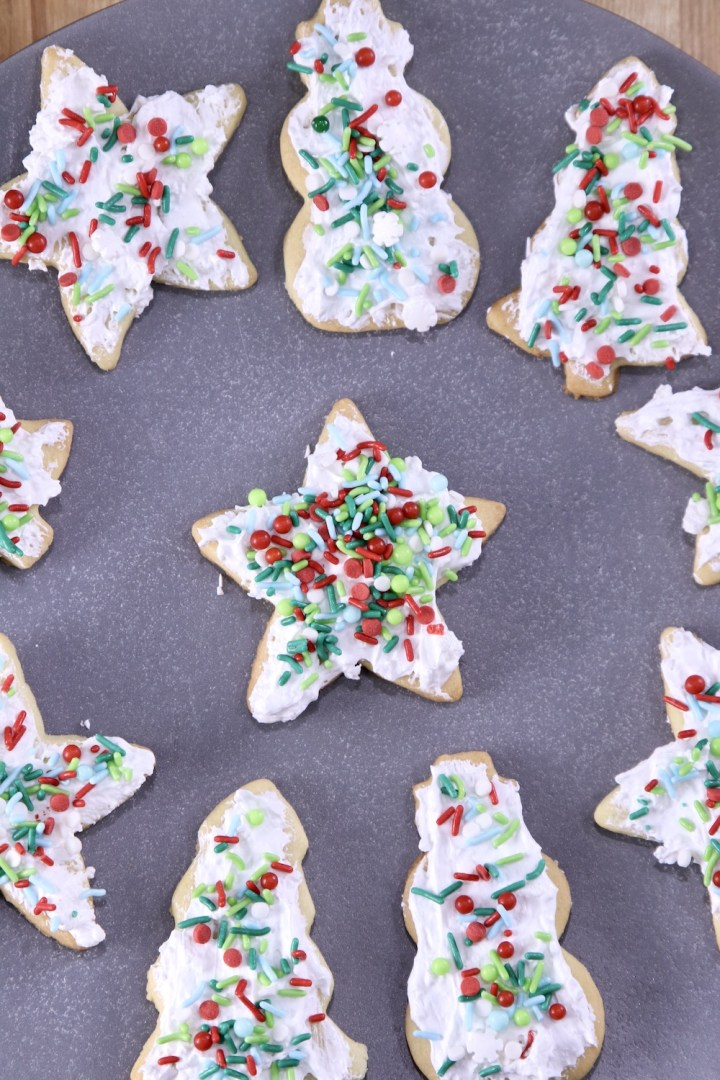 Platter of iced sugar cookies with sprinkles. Christmas shapes - trees, stars, snowmen