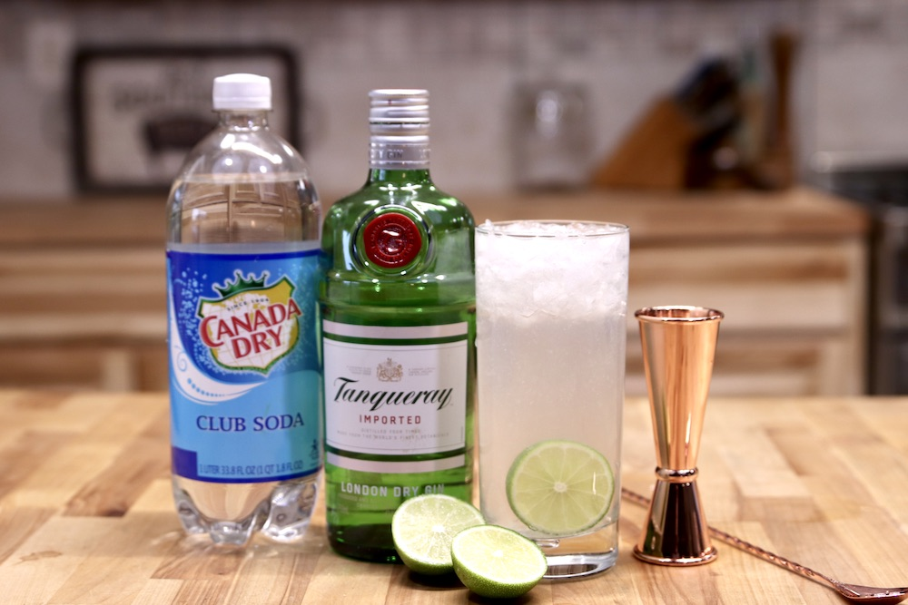 Ingredients for Gin Rickey Cocktail: club soda, gin, limes, with the cocktail