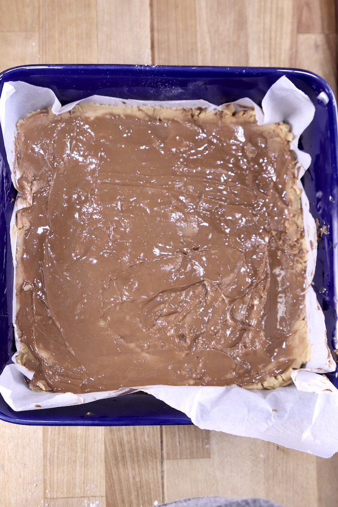 Peanut Butter Cup Fudge with melted chocolate on top - in a blue baking dish