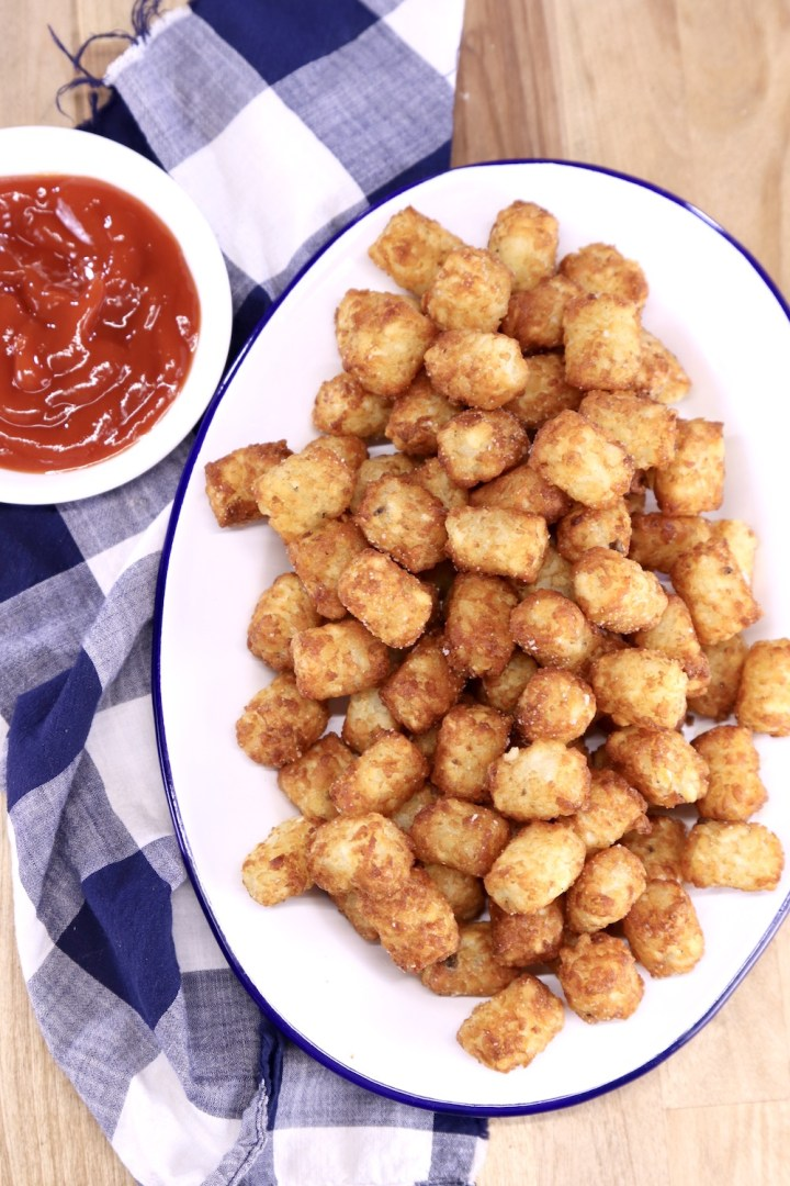 oval platter of tater tots with small bowl of ketchup
