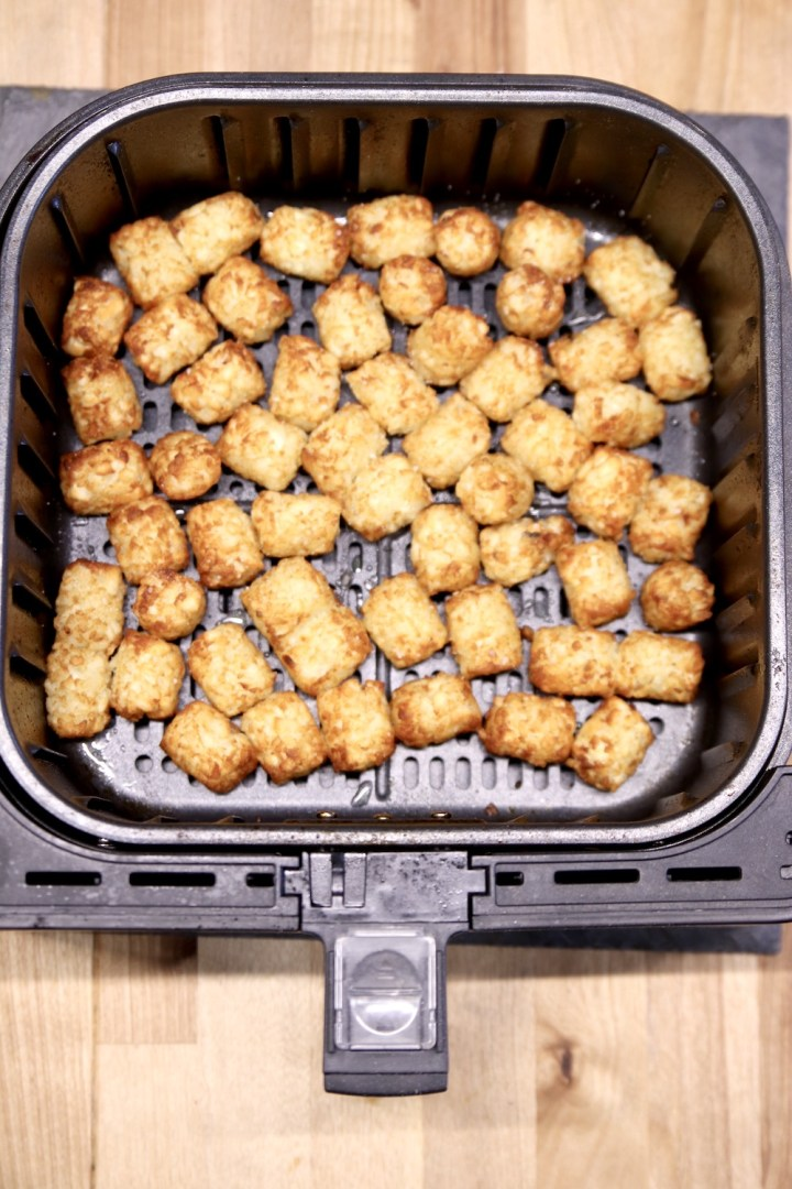 Air fryer basket with browned tater tots