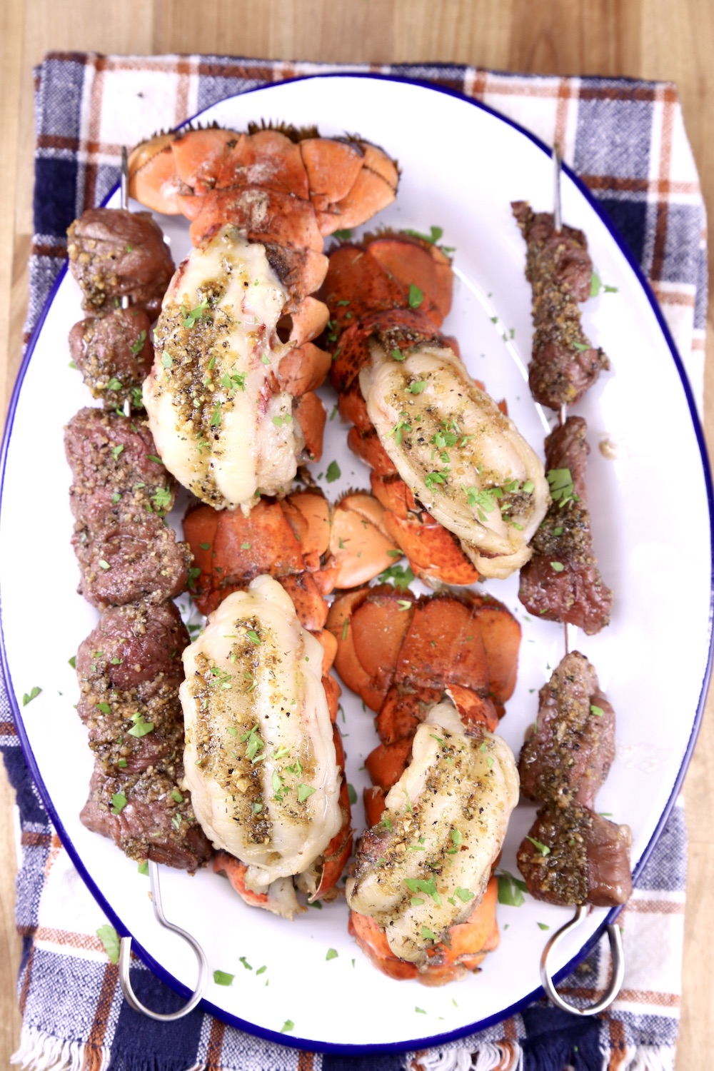 Plaid napkin with oval platter of grilled garlic butter lobster and steak bites