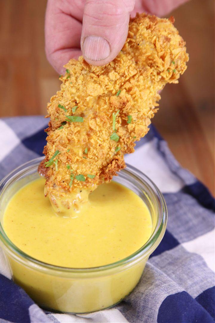 Cornflake chicken tender dipping in honey mustard sauce