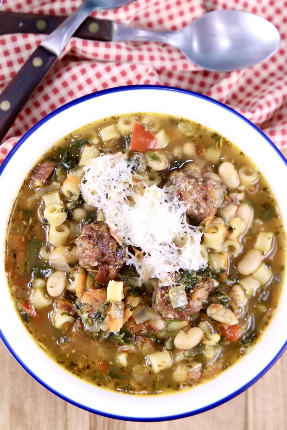 Meatball Soup with parmesan cheese grated over the top, spoons, red check napkin