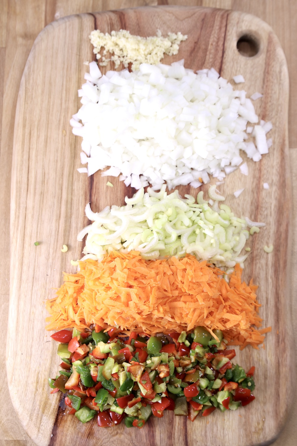cutting board with garlic, onions, celery, carrots, diced peppers