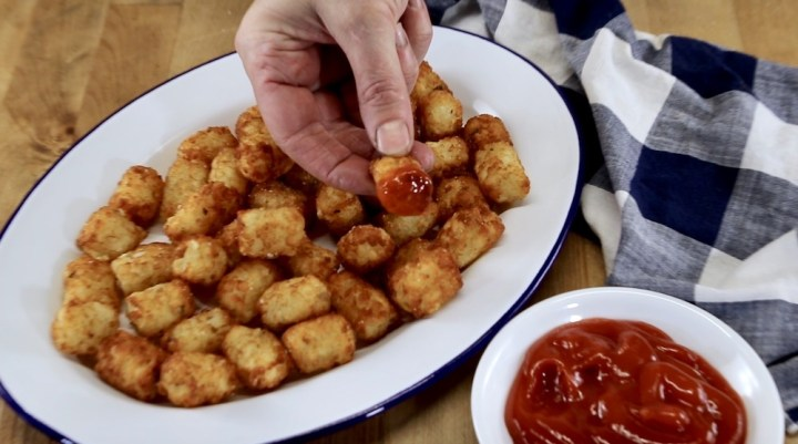 platter of tater tots with one dipped in ketchup