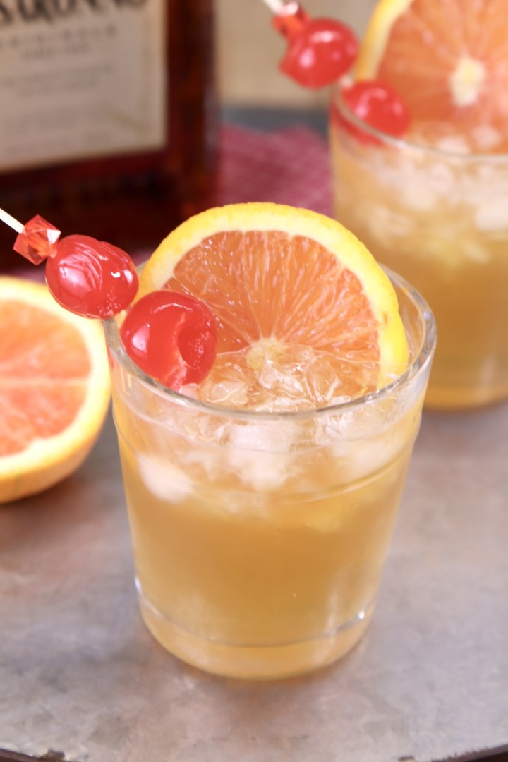 Amaretto Sour Cocktail with cherry and orange slice garnish
