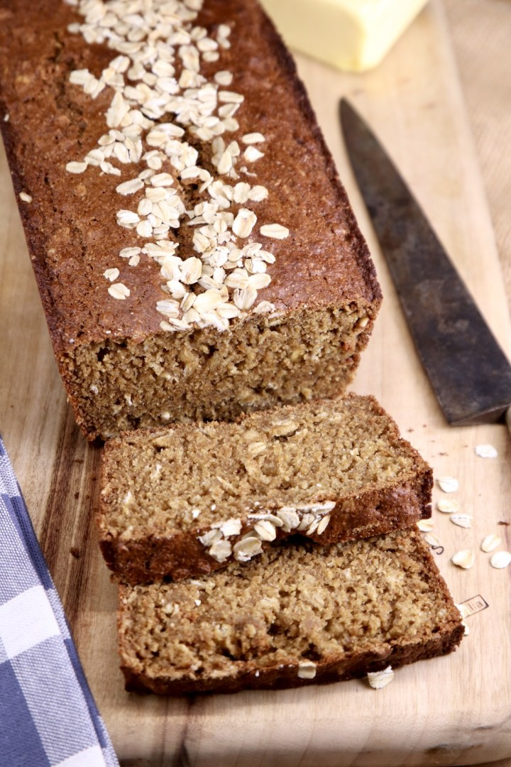 cutting board and knife with loaf of sliced brown bread with oat topping