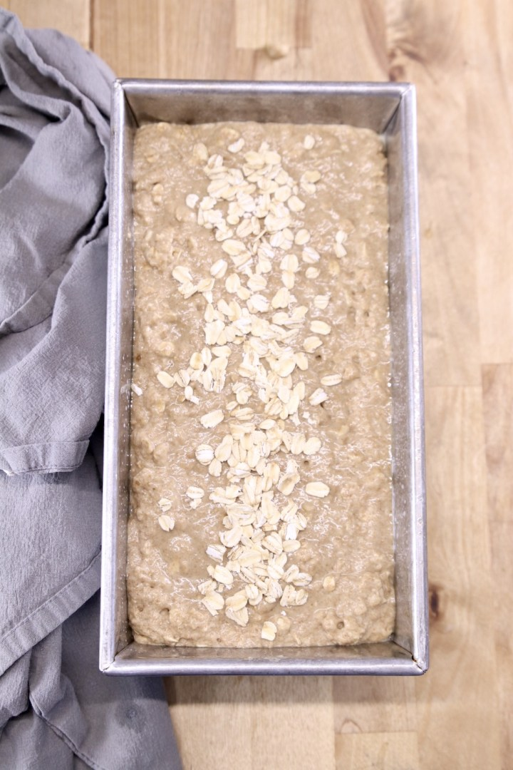 loaf pan with brown bread batter topped with a few oats