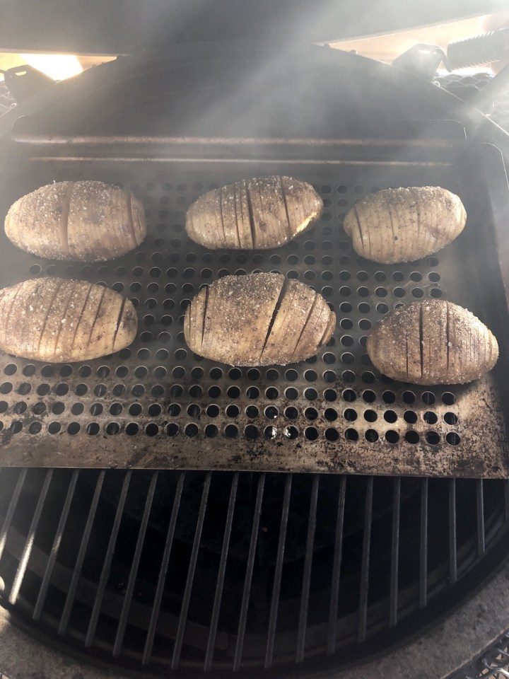 Grill with pan of fan sliced potatoes