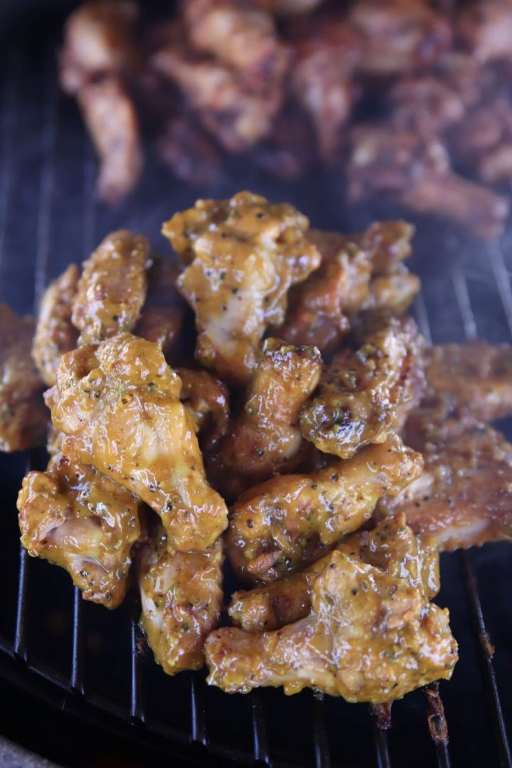 Chicken wings with mustard BBQ sauce on a grill