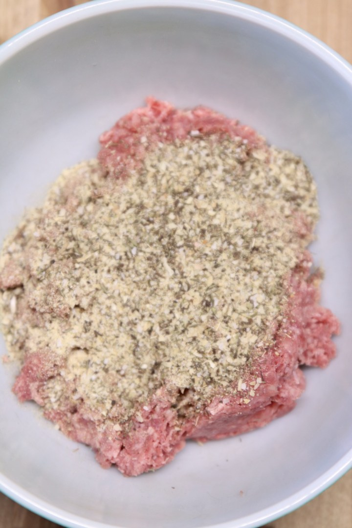 ground beef and spices in a bowl for meatballs