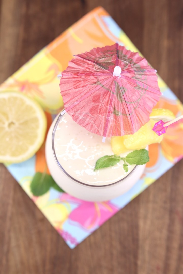 Overhead view of frozen lemonade cocktail with drink umbrella on a flowered napkin