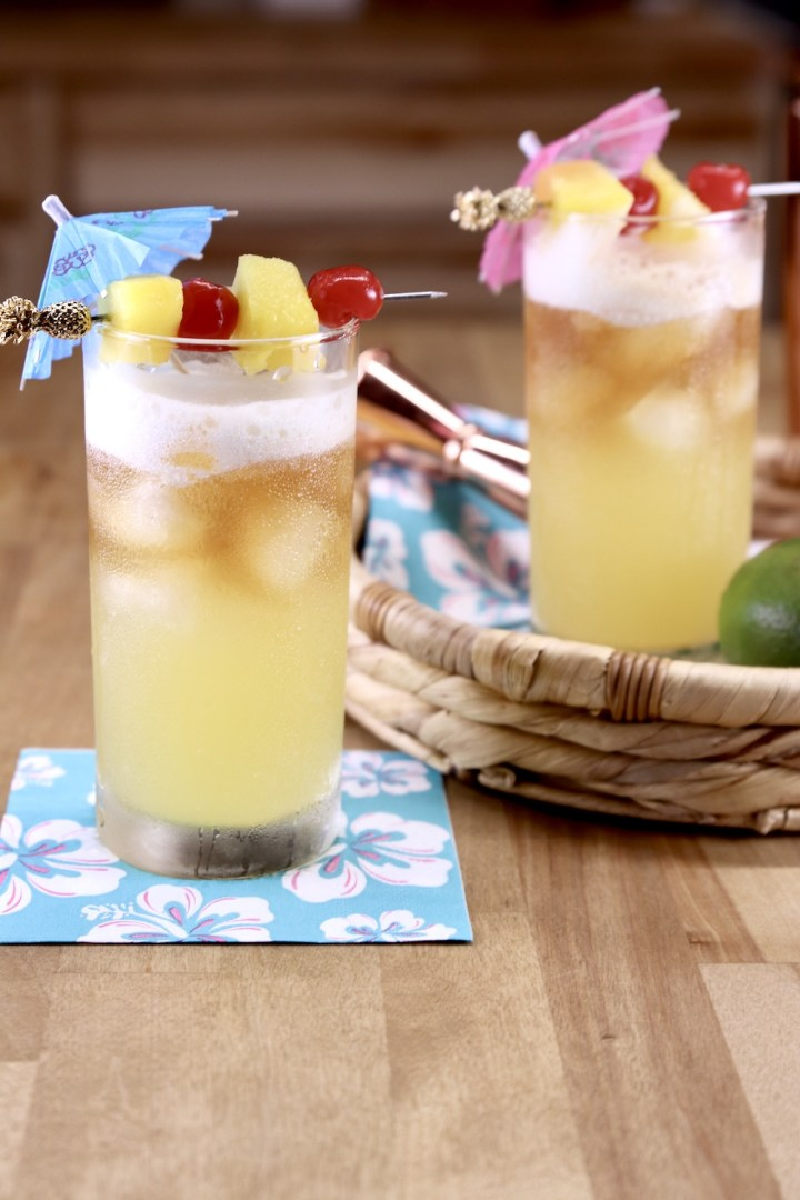2 Mai Tai cocktails garnished with pineapple and cherries