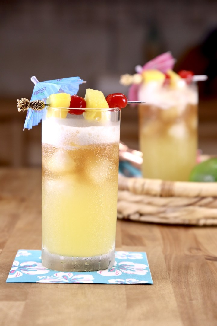 Mai Tai Cocktails with drink umbrellas, cherries and pineapple garnish