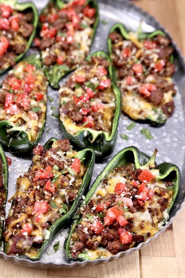 Poblano peppers stuffed with sausage and cheese topped with tomatoes