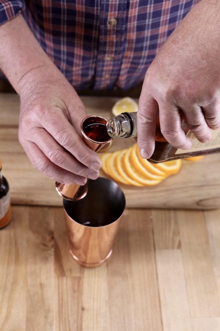 pouring amaretto into a jigger